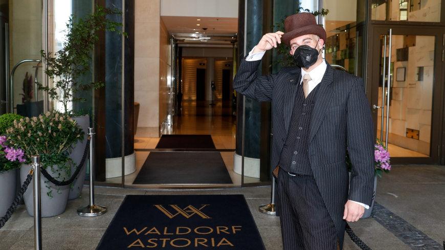 Portier im Waldorf Astoria Berlin übt Begrüßung der Freizeitgäste